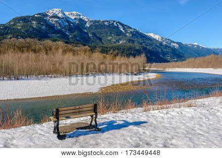 Majestic mountain river in winter over snow mountains and blue sky in Vancouver, Canada. Wooden bench in a park.