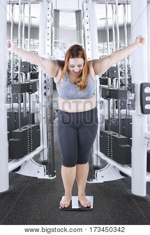Portrait of a joyful overweight girl with blonde hair standing on a weighing scale while expressing her success at gym