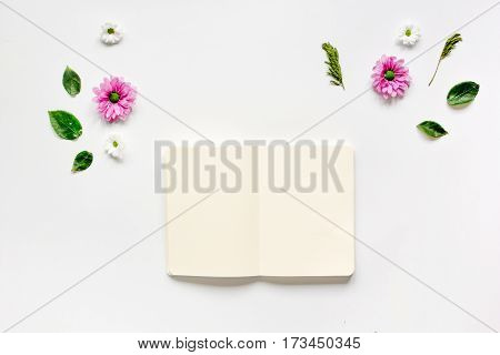 Bright flower petals and white paper notebook on white table background top view mock-up