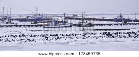 Caraquet, New Brunswick, February 5, 2017 -- Close up of snow covered fishing boats docks and frozen waters of Chaleur Bay at Caraquet, New Brunswick on a chilly overcast day in February.