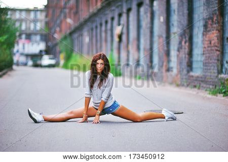 Young pretty girl sitting on twine on the sidewalk in the courtyard of a brick building. The concept of a healthy lifestyle.