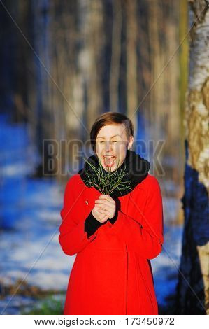 portrait of a happy young woman with closed eyes and wide open mouth in a red coat with a green sprig in hand on a blurred background of a winter Park at sunset