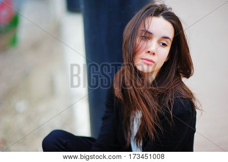Young long-haired brunette girl is sitting shredded in the wind hair and a melancholy sight on the street on a summer day.