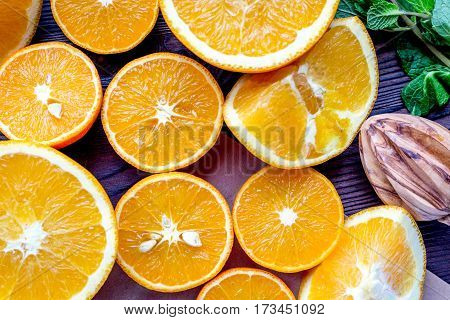 Bright orange juice making from fruit and fresh mint leaves on wooden kitchen table background top view