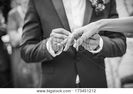 The groom wears a ring for bride. black and white photo.