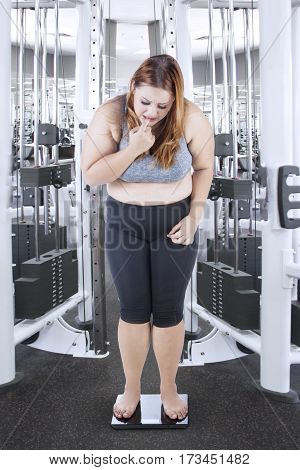 Overweight girl with blonde hair measuring her weight with a weighing scale and looks stressful