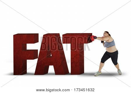 Overweight woman wearing boxing gloves while punching stones shaped word of fat