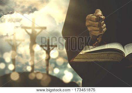 Christian person holding a bible and rosary with crucifixion sign on the background
