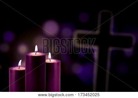 Picture of three purple candles glowing with a cross symbol and bokeh background