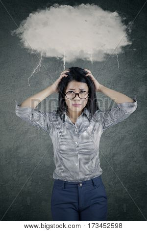 Portrait of a young businesswoman looks stressful standing under cloud speech bubble