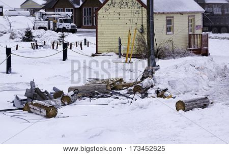 Caraquet, New Brunswick, February 5, 2017 -- Sawed off pieces of a telephone pole are strewn across the snow cover ground after the ice storm at Caraquet, New Brunswick on a chilly overcast day in February.
