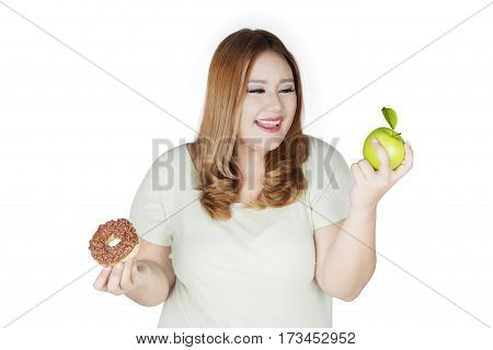 Young woman with blonde hair choosing between apple and donut. Isolated on white background