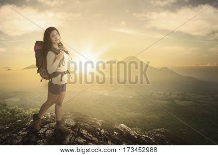 Young woman hiker holding backpack while standing on the rock with sunset and mountain in the background
