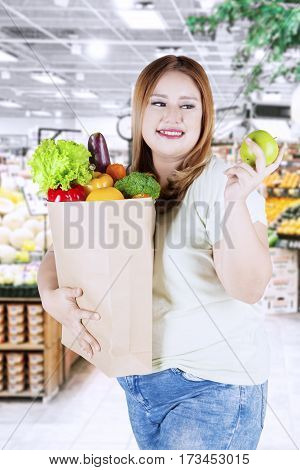 Overweight woman with blonde hair holding a green apple fruit and shopping bag full of vegetables in the supermarket