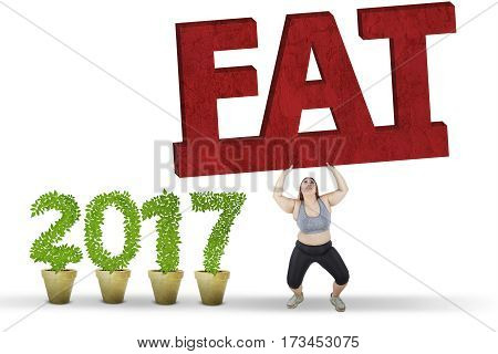 Overweight woman lifts a fat word while wearing sportswear near number 2017 isolated on white background