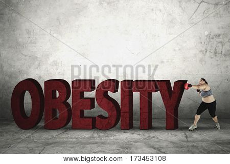 Portrait of young fat woman is wearing boxing gloves while punching word of obesity