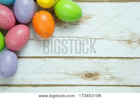 Colorful speckled Easter eggs on a whitewashed wood plank board with room for copy space