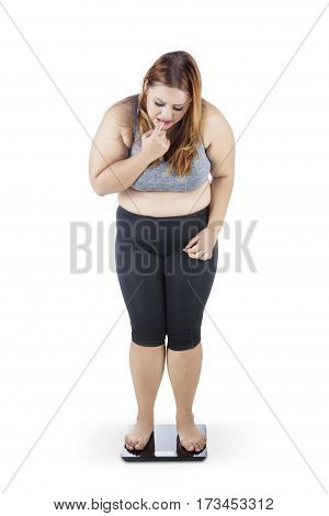Full length of overweight woman with blonde hair standing on weighing scale and looks worried