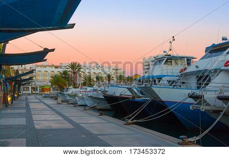 Magnificent magenta sunset color in marina harbor.  End of a warm sunny day in Ibiza, St Antoni de Portmany, Spain.