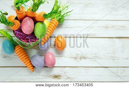 Whimsical Carrots and Easter Eggs in a pastel basket on a wood plank background board with room for copy space