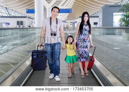 Portrait of young happy family carrying luggages while walking on the airport escalator
