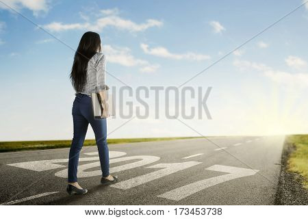 Image of young female student holds a laptop while walks on the road with numbers 2017