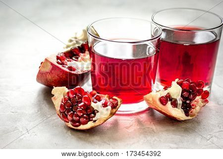 pomegranate juice with seed of sliced fruit on kitchen stone table background