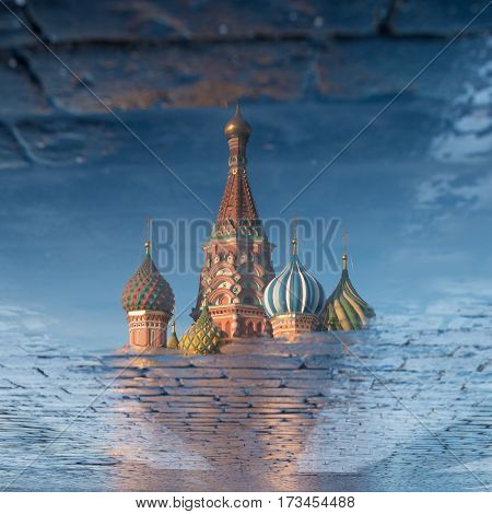 St. Basil's Cathedral on Red square in spring day reflected in the puddle. Moscow, Russia.