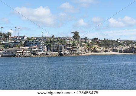 NEWPORT BEACH, CALIFORNIA - FEBRUARY 22, 2017: Corona Del Mar. Homes along the Newport-Avalon Channel in Southern California, viewed from the Newport jetty.