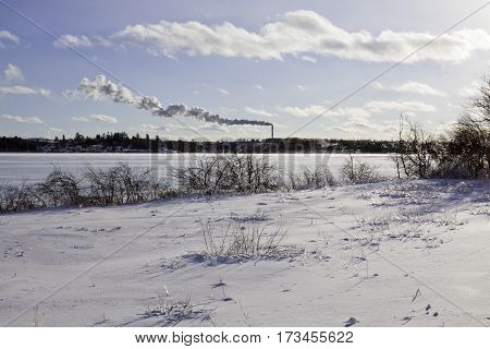 Winter snow scene snow covers a small field of bare branches and bushes are covered in thick ice from a recent ice storm. In the distance across the frozen Miramichi River an industry billows smoke shot in New Brunswick on a chilly bright blue sky sunny