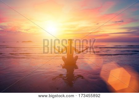 Sunset yoga on the beach, abstract photo about healthy lifestyle.