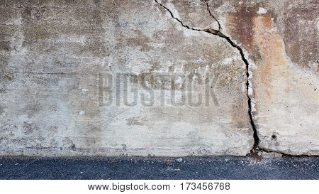 Big crack in old messy concrete wall