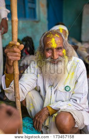 Nandgaon, India - March 18, 2016: Portrait of an unidentified man with face smeared with colors during Holi celebration in Nandgaon, Uttar Pradesh, India.
