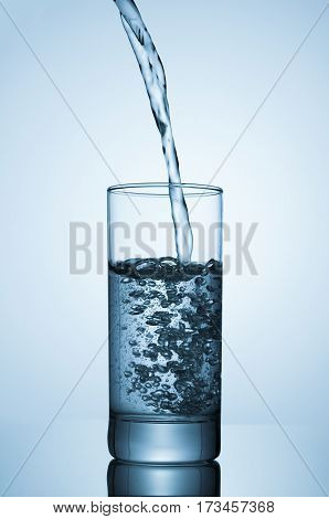Sparkling water pouring into glass on blue background