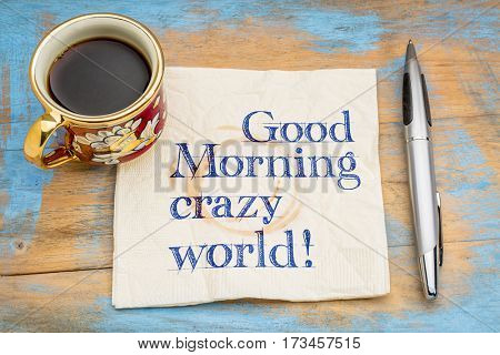 Good Morning crazy world - handwriting on a napkin with a cup of espresso coffee