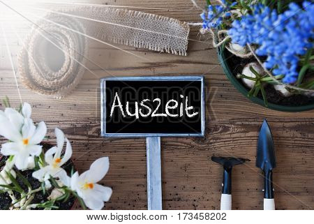 Sign With German Text Auszeit Means Downtime. Sunny Spring Flowers Like Grape Hyacinth And Crocus. Gardening Tools Like Rake And Shovel. Hemp Fabric Ribbon. Aged Wooden Background