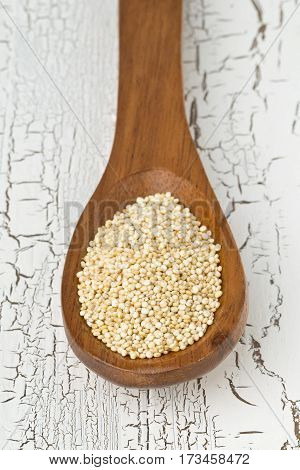 Raw unprocessed quinoa seeds in wooden spoon on white rustic wooden table