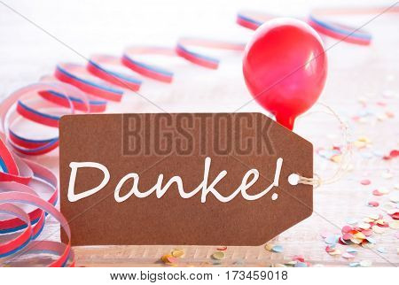 One Label With German Text Danke Means Thank You. Party Decoration Like Streamer, Confetti And Balloon. Wooden Background With Vintage, Retro Or Rustic Syle