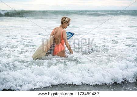 Pretty blonde girl with short hairstyle stands sideways in the waves on the beach on the background of the sea and the cloudy sky. She wears orange swimsuit with sunglasses and holds the surfboard.