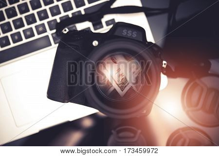 Microstock Photo Business Concept Photo with Digital Camera and Dollar Banknotes Reflection Inside the Lens and Laptop Computer. Making Money Taking Pictures.