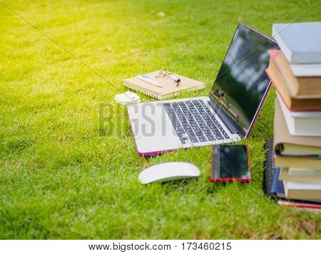 Laptop, notebook, smart phone and stack of old tattered book on the green grass