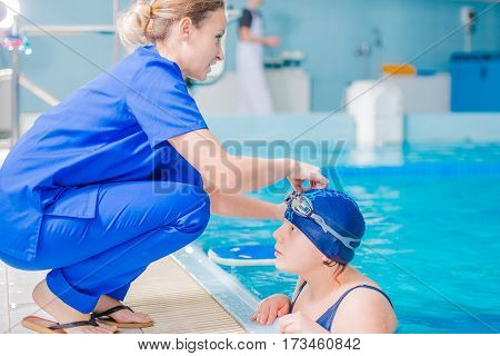 Rehabilitation in Swimming Pool. Medical Staff Supervising Children Rehabilitation in the Rehabilitation Center Pool.