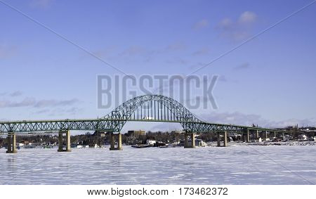 Winter snow scene, Centennial Bridge crossing over the Miramichi River, New Brunswick, to Chatham, with buildings and commerce in the background on a chilly bright, blue sky, sunny day in February.