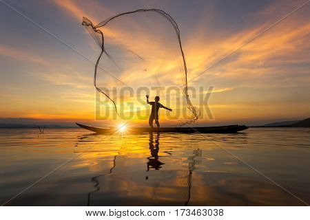 Silhouette of Myanmar fisherman on wooden boat Myanmar fisherman in action catching freshwater fish in nature river Myanmar traditional fishermen at the sunset near Inle lakeMyanmar