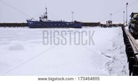 Caraquet, New Brunswick, February 5, 2017 -- Close up of a large shipping boat at the snow covered docks in the frozen waters of Chaleur Bay at Caraquet, New Brunswick, on a chilly overcast day in February.