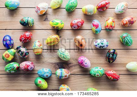 Easter handmade eggs painted in colorful floral patterns placed on wooden table. Traditional decoration, handmade design.