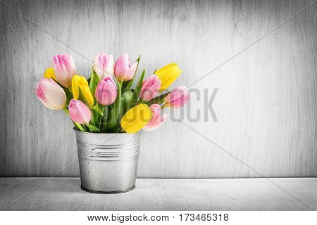 Fresh bouquet of tulips in a metal pot on rustic wood. Copyspace and vignette.