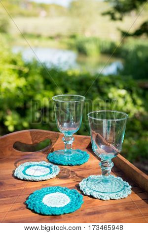 Glass Goblets On Knitted Woolen Coasters In Wooden Tray Outdoors