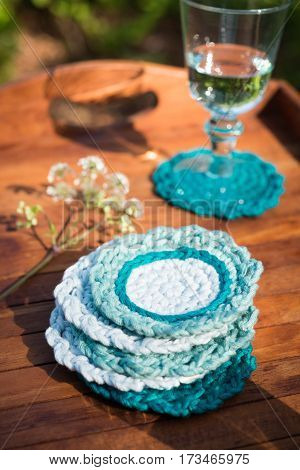 Pile Of Round Knitted Woolen Coasters In Wooden Tray