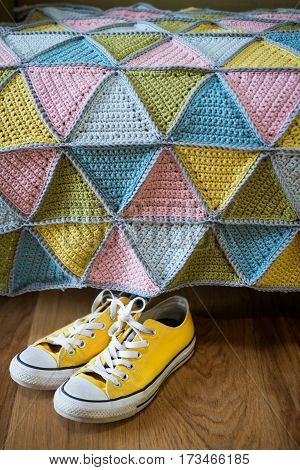 Pair Of Yellow Sneakers Under A Colorful Knitted Mat